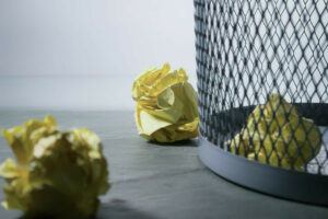 crumpled up paper in a wastebasket, rejected writing