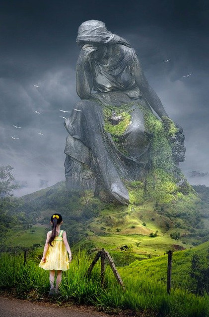 little girl looking up at huge statue of Mother Earth